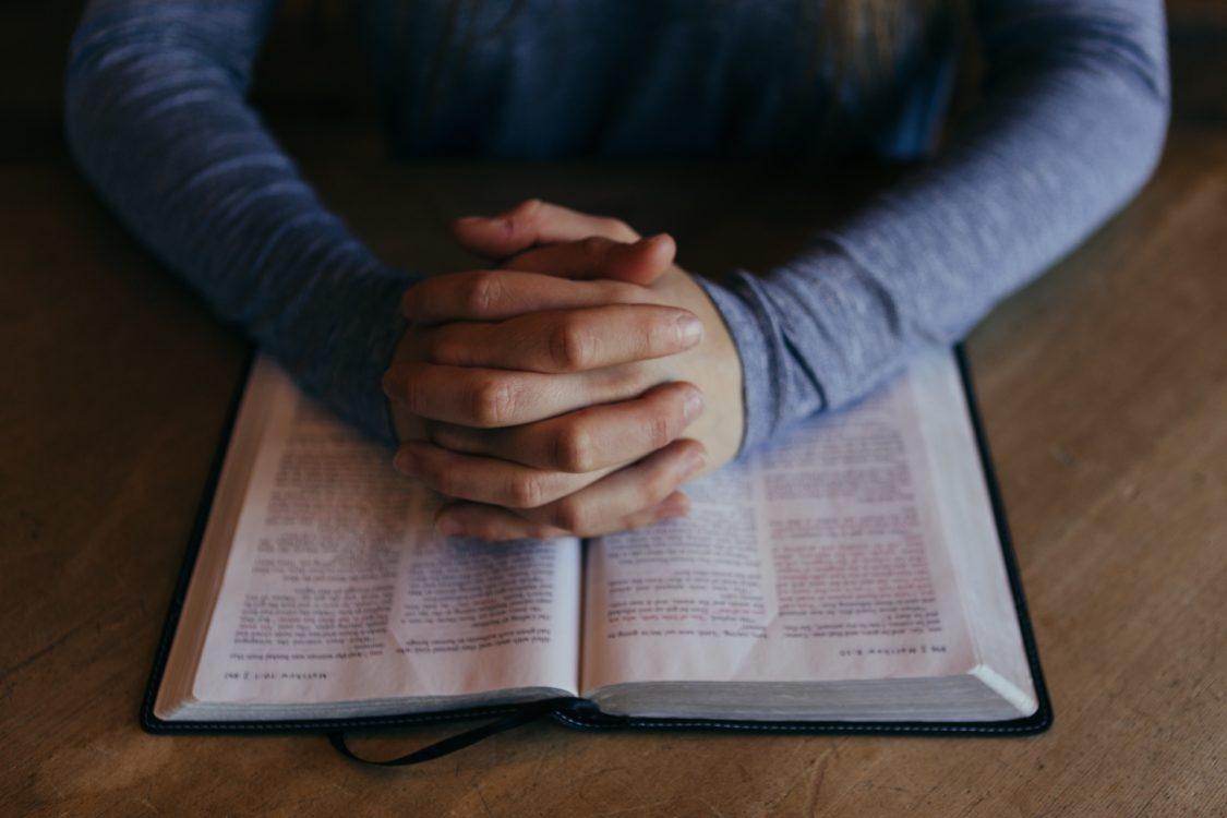 betende Hände auf einer geöffneten Bibel