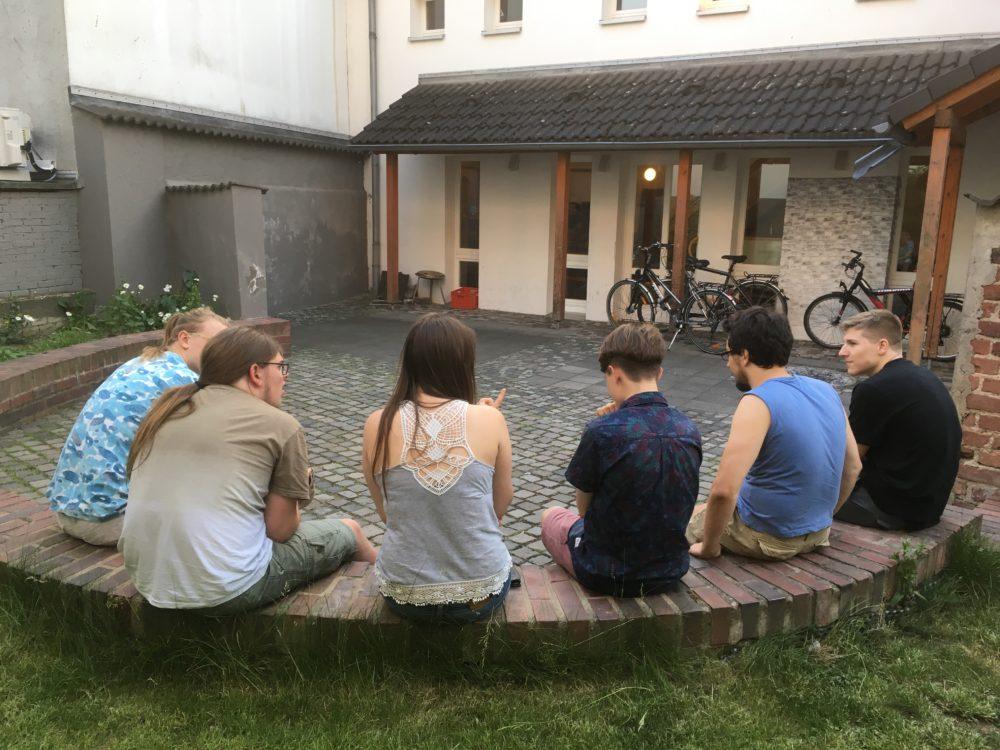 Jugendliche auf der Mauer vor dem Jugendhaus