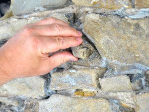 Eine Hand nimmt einen Stein aus dem Putz der Turmfassade.