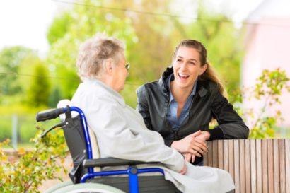 eine junge Frau unterhält sich mit einer Frau im Rollstuhl