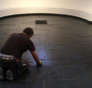 Ein Mitarbeiter oelt den Schieferboden in der Apsis (Altarraum) der Reformationskirche