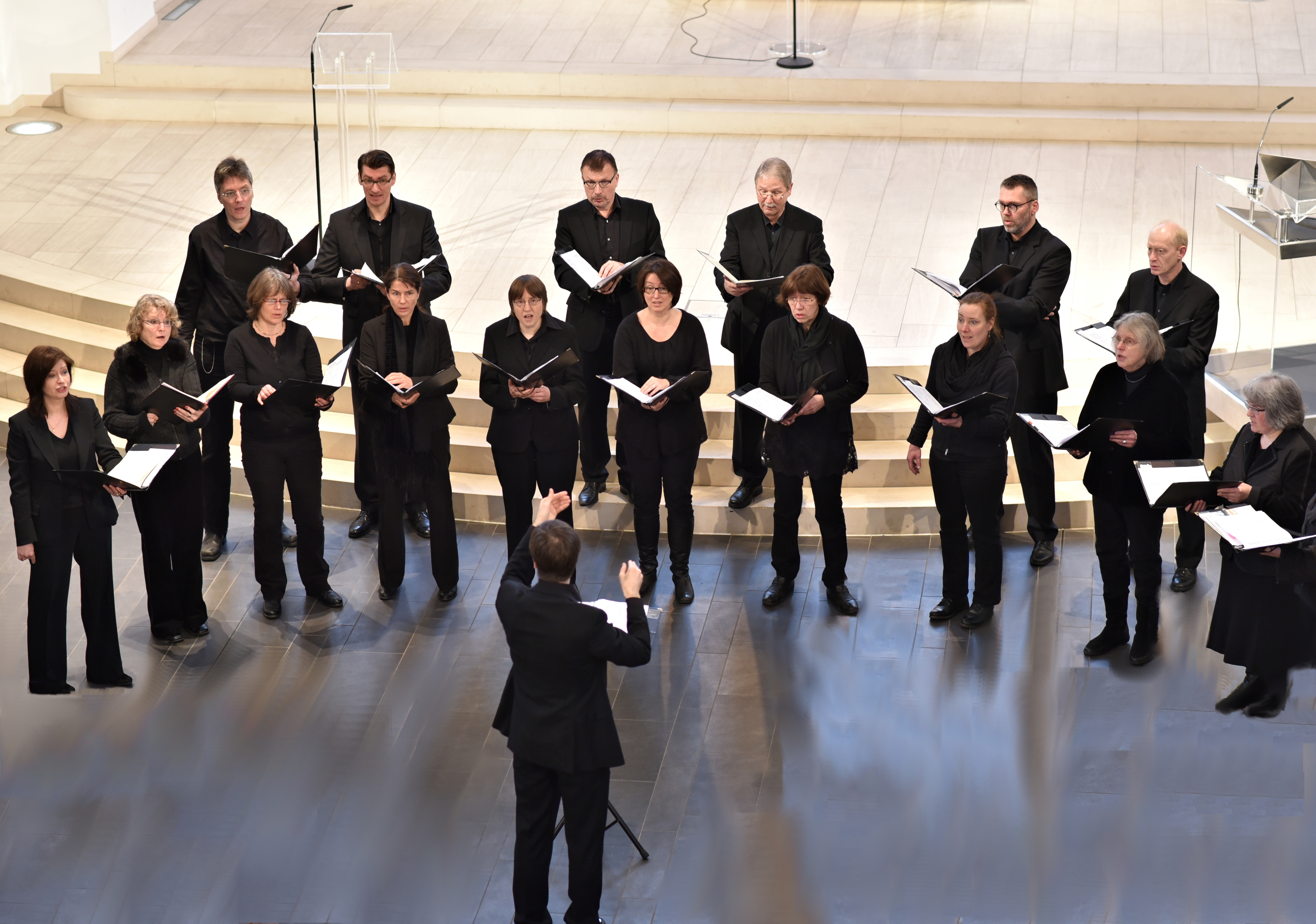 Vor dem Chorleiter, der nur in Rückenansicht zu sehen ist, stehen die Sängerinnen des Kammerchores in schwarzer Kleidung und singen aus schwarzen Mappen.