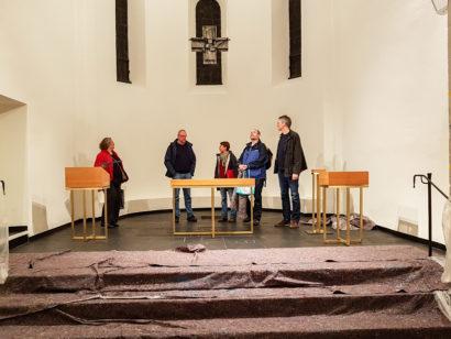 Fünf Personen vor dem neuen Lesepult, Abendsmahlstisch, Taufbecken und dem Kerzenständer aus gebürstetem Messing mit Birkenholzoberteilen
