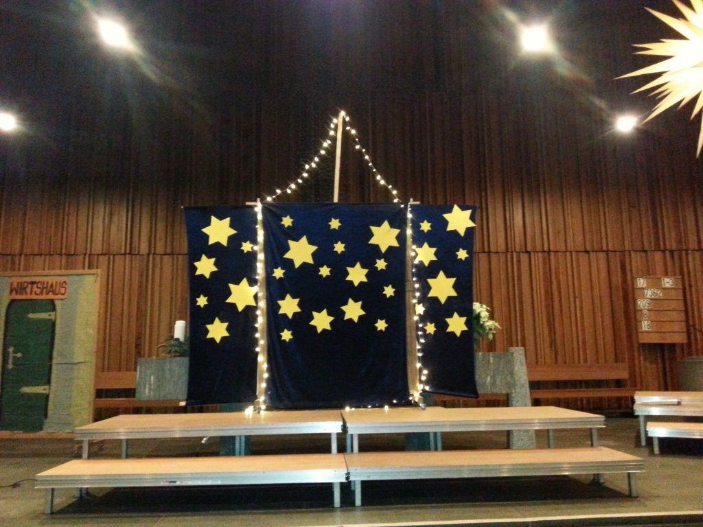 Das Bild zeigt die Altarempore in der Friedenskirche in Hilden. Der Altar ist fast komplett von eihem Hintergrundbild für das Krippenspiel verdeckt. Es ist schwarzblau mit gelben Sternen.