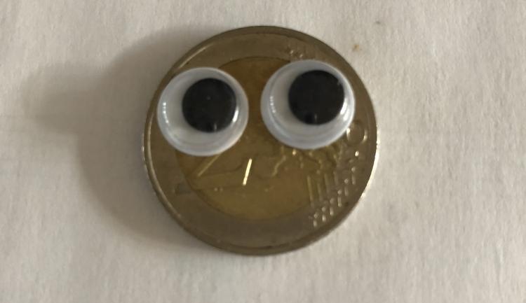 Euro-Münze mit aufgeklebten Augen