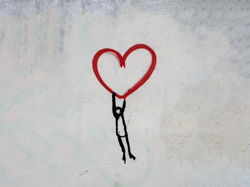 Graffiti an einer Betonwand: Ein Mensch wird von einem Herzen in die Luft gehoben
