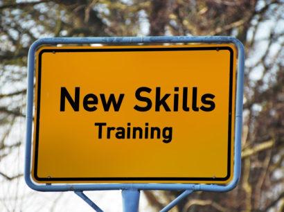 """Ortseingangsschild mit Beschriftung """"New Skills"""" Training"""