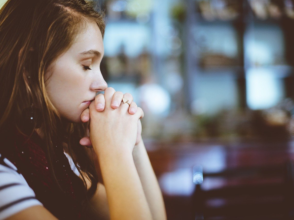 Junge Frau betet mit geschlossenen Augen