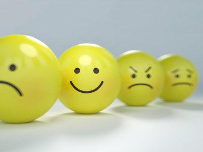 gelbe Bälle mit Gesichtern unterschiedlicher Gefühlsausdrücke