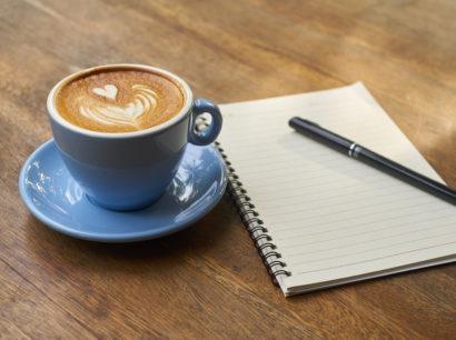 Kaffee und Schreibblock auf Holztisch