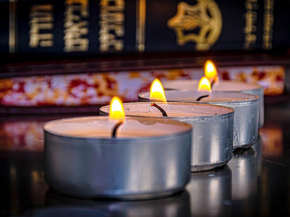 Kerzen vor einem Buch mit hebräischen Schriftzeichen