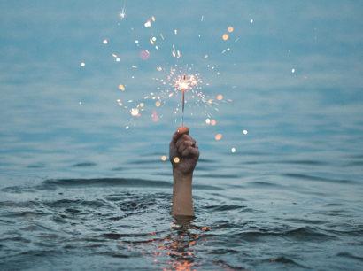 eine Hand ragt aus dem Wasser und hält eine brennende Wunderkerze