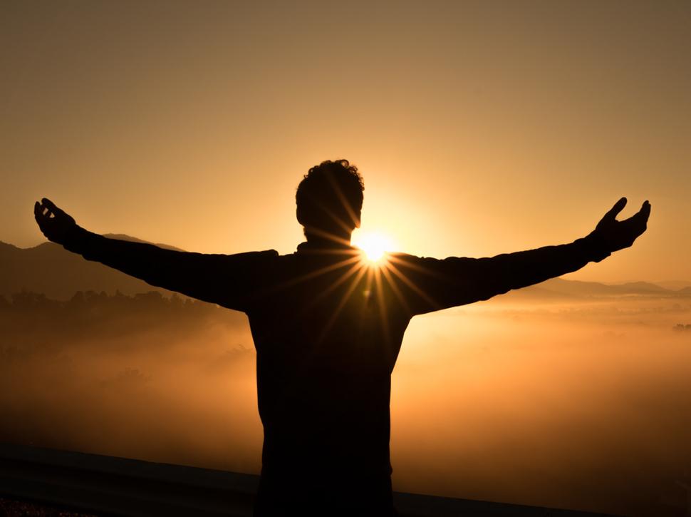 Mensch mit ausgebreiteten Armen der Sonne entgegen