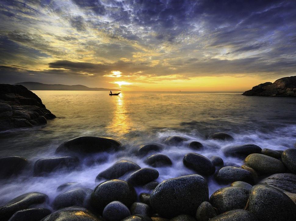 Stilles Meer mit dramatischem Himmel im Sonnenuntergang
