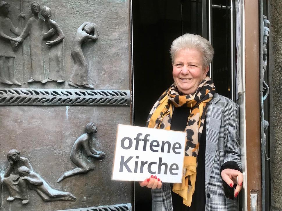 """Anne de Wendt mit dem Schild """"offene Kirche"""" im Eingangsportal der Reformationskirche"""
